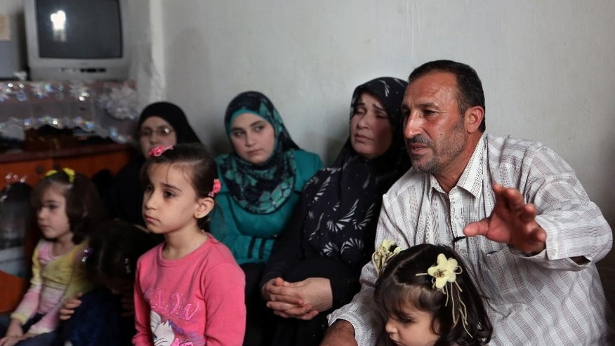In this Thursday, Nov. 20, 2014 photo, Mohammed Aloun, 43, right, speaks during an interview with The Associated Press as he sits with his family at their house in the northern port city of Tripoli, Lebanon. The Alouns are one of several Syrian families who were given asylum in Uruguay after its government offered to accept 120 refugees. It's a small number compared to the 3 million Syrians who have fled the conflict, now in its fourth year, crowded into overwhelmed neighboring countries or who tried to reach Europe. (AP Photo/Bilal Hussein)
