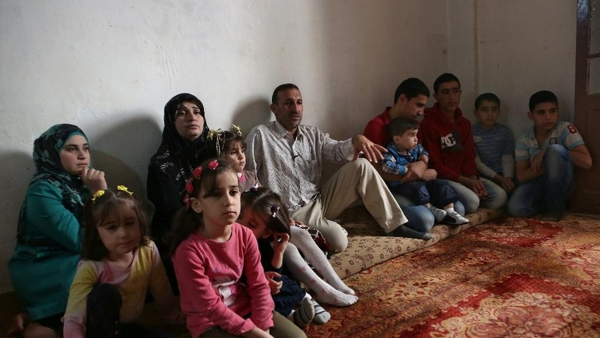 In this Thursday, Nov. 20, 2014 photo, Mohammed Aloun, 43, center, speaks during an interview with The Associated Press as he sits with his family at their house in the northern port city of Tripoli, Lebanon. The Alouns are one of several Syrian families who were given asylum in Uruguay after its government offered to accept 120 refugees. It's a small number compared to the 3 million Syrians who have fled the conflict, now in its fourth year, crowded into overwhelmed neighboring countries or who tried to reach Europe. (AP Photo/Bilal Hussein)