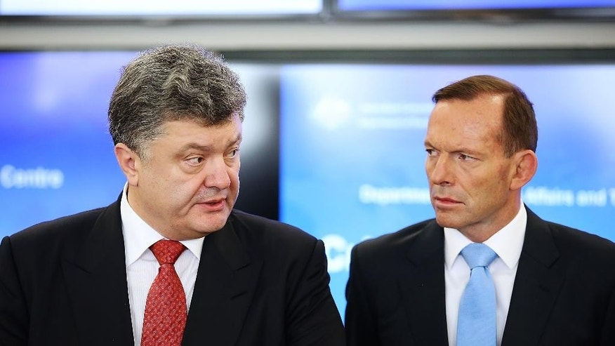 Ukrainian President Petro Poroshenko, left, speaks as Australian Prime Minister Tony Abbott listens in the Crisis Management Centre at the Department of Foreign Affairs and Trade in Canberra, Australia Friday, Dec. 12, 2014. (AP Photo/Stefan Postles, Pool)
