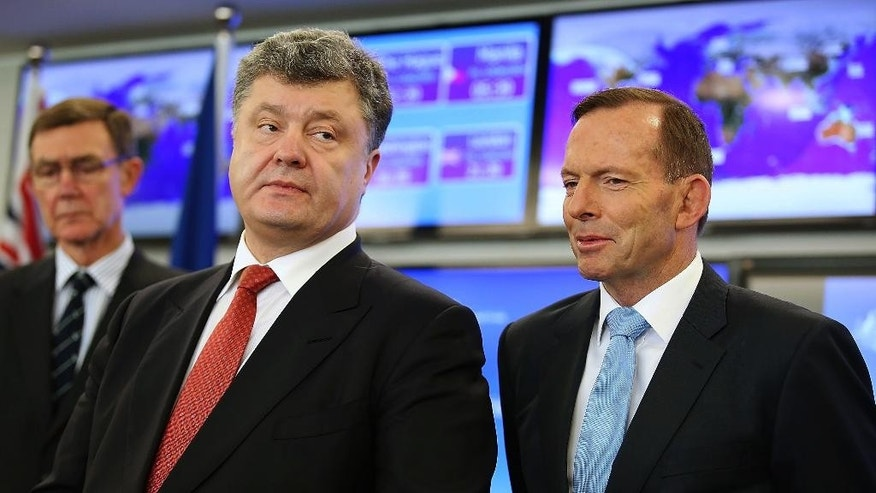 Ukrainian President Petro Poroshenko, center, speaks as Australian Prime Minister Tony Abbott, right, listens in the Crisis Management Centre at the Department of Foreign Affairs and Trade in Canberra, Australia Friday, Dec. 12, 2014.  (AP Photo/Stefan Postles, Pool)