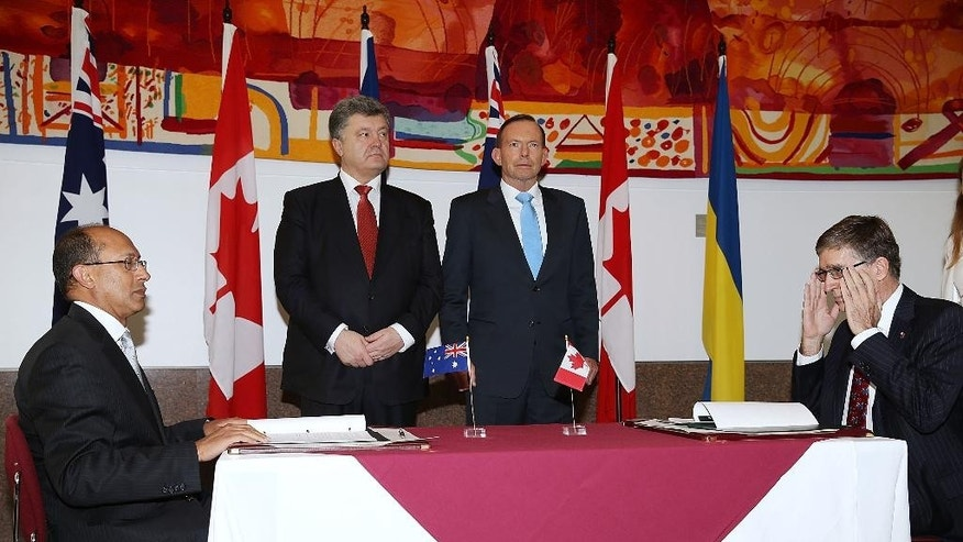 Ukrainian President Petro Poroshenko, second left, and Australia Prime Minister Tony Abbott, second right, witness the signing of an agreement between Canada and Australia in relation to a new joint embassy to be built for the two countries in the Ukraine, at the Department of Foreign Affairs and Trade in Canberra, Australia Friday, Dec. 12, 2014. (AP Photo/Stefan Postles, Pool)