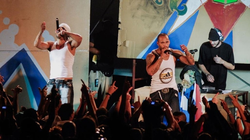 In this April 23, 2010 photo, members of Los Aldeanos, Aldo Rodriguez, left, and Bian Rodriguez, center, perform in concert at the Acapulco Theater in Havana, Cuba. Documents obtained by The Associated Press show that a U.S. agency infiltrated Cuba's hip-hop scene, recruiting unwitting rappers to spark a youth movement against the government. (AP Photo)