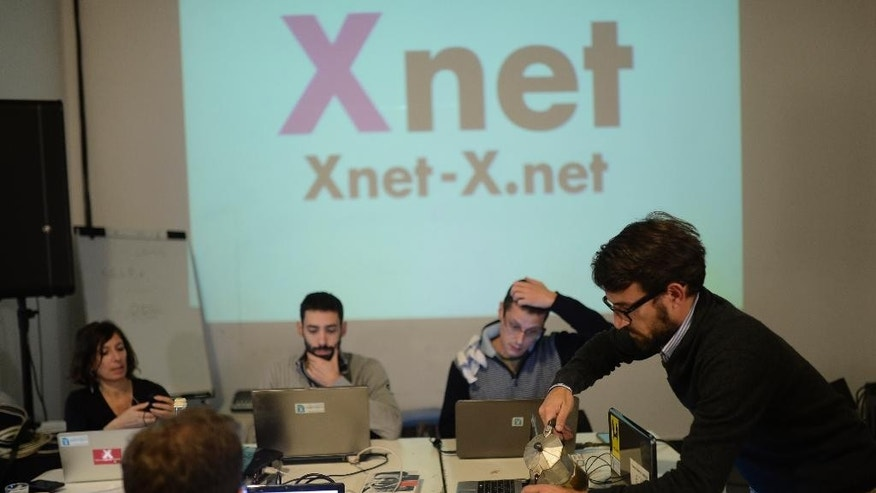 In this image taken on Wednesday, Dec. 3, 2014, Pau Lopez. 35, right, prepares a coffee with his teammates in the office in Barcelona, Spain. The XNet platform was inspired by Wikileaks, which puts secret information online. But it has gone further, by working on three fronts: activism, politics and through the courts. More than 200 volunteers are involved. Setting up an online drop box for citizens' complaints has paid off, exposing some of Spain's biggest corruption scandals. At a time when numerous official investigations are under way into corruption cases affecting Spain's main political parties and members of the monarchy, with murky relationships between leading public figures and businessmen coming to light, many government workers have turned to this platform as a safe way of exposing irregularities based on official documents. (AP Photo/Manu Fernandez)