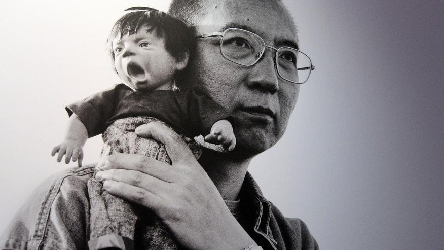 "FILE - In this Tuesday, Feb. 7 2012 photo shows 2010 Nobel Peace Prize winner Liu Xiaobo holding a doll in a detail of a photograph by his wife, Chinese artist Liu Xia on display at during a preview of ""The Silent Strength of Liu Xia"" exhibit at The Italian Academy in Columbia University in New York. The jailed Chinese Nobel Peace Laureate Liu Xiaobo has told a friend that he hopes the world could pay more attention to lesser known Chinese activists. (AP Photo/Mary Altaffer)"