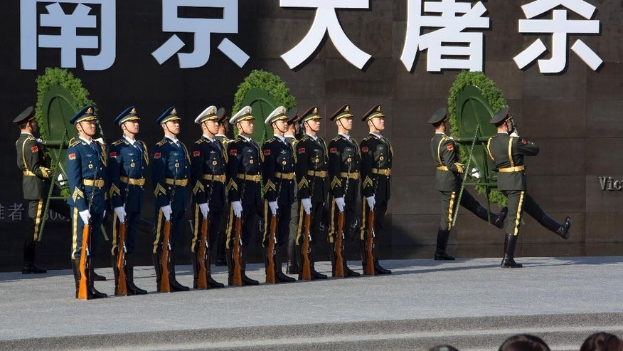 "Chinese honor guard members take part in a ceremony to mark China's first National Memorial Day at the Nanjing Massacre Memorial Hall in Nanjing in eastern China's Jiangsu province Saturday, Dec. 13, 2014. Chinese President Xi Jinping and other Chinese leaders presided Saturday at the ceremony on the 77th anniversary of the Nanking massacre amid a drive to revive memories of Japan's brutal invasion and stir patriotism. Chinese characters in white reads ""Nanjing Massacre"". (AP Photo/Ng Han Guan)"