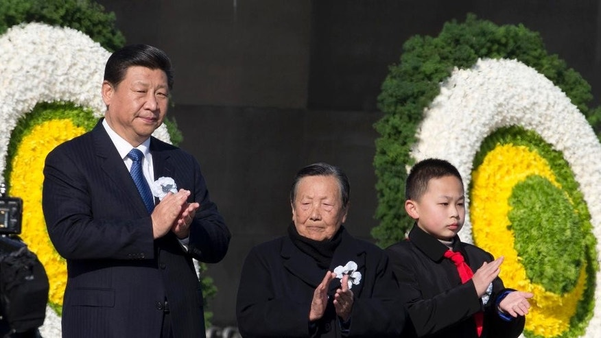Chinese President Xi Jinping, left, attends a ceremony to mark China's first National Memorial Day at the Nanjing Massacre Memorial Hall in Nanjing in eastern China's Jiangsu province Saturday, Dec. 13, 2014. Xi and other Chinese leaders presided Saturday at the ceremony on the 77th anniversary of the Nanking massacre amid a drive to revive memories of Japan's brutal invasion and stir patriotism. (AP Photo/Ng Han Guan)