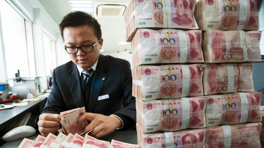 Dec. 2, 2014: A clerk counts Chinese 100 yuan banknotes at a branch of China Construction Bank in Nantong, Jiangsu province.