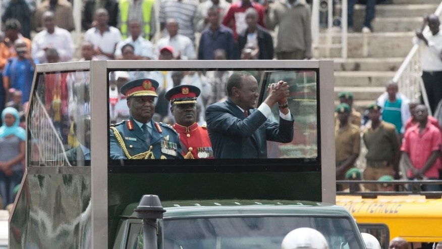 Kenyan President, Uhuru Kenyatta, right, with Chief of Defence Forces, Julius Karangi, left, waves to the crowd in his bullet proof Land Rover as he arrives at the Nyayo National Stadium Nairobi, Kenya Friday, Dec. 12, 2014, during the 51st Madaraka Day or Independence from British Rule celebrations. (AP Photo Sayyid Azim)