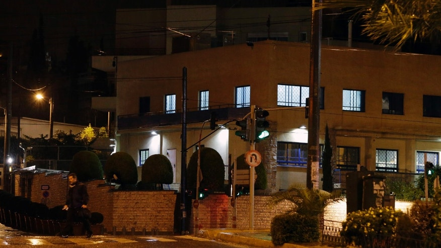 Dec. 12, 2014: Lights are on at Israeli Embassy as a plain clothed police officer passes in Athens, early Friday.