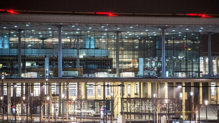 The terminal of the new Berlin airport,  'Berlin Brandenburg Willy Brandt'  is illuminated  in Schoenefeld near Berlin early Friday Dec. 12, 2014.  Berlin's new airport should be open within three years - barring further unforeseen problems. German news agency dpa quoted Rainer Bretschneider, the deputy chairman of the airport's supervisory board, saying that it will begin operating in the second half of 2017. The airport was first scheduled to be ready late 2011 but that and three other opening dates were canceled due to technical problems. Costs, meanwhile, have more than doubled to some 5.4 billion euros (US $7.1 billion). (AP Photo/dpa,Patrick Pleul)
