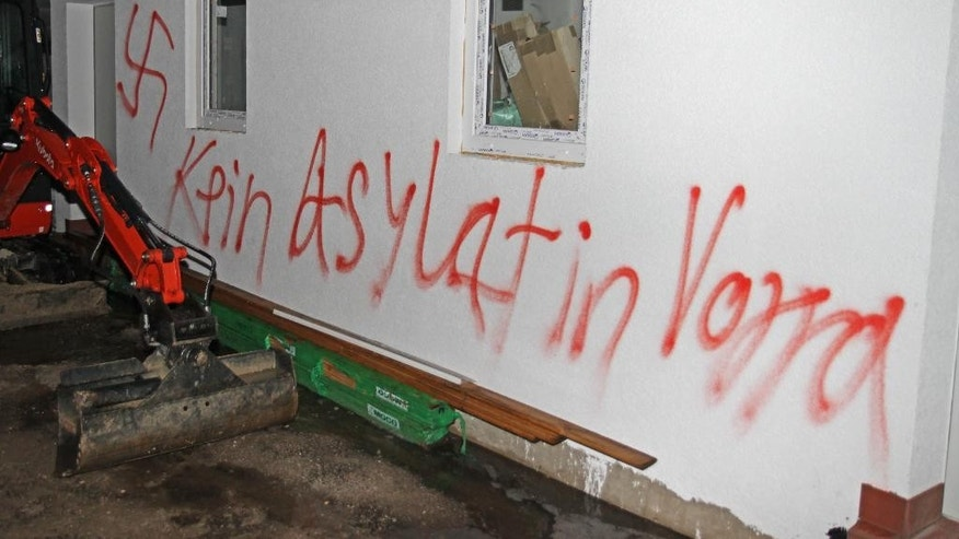 A swastika and the words 'No asylum seeker in Vorra,' are written on a building  in Vorra, Germany, early Friday Dec. 12, 2014.  Police say arsonists are suspected of setting fires at three empty buildings in Bavaria that had been earmarked to serve as accommodation for asylum seekers. The fires broke out late Thursday evening in Vorra, near Nuremberg. Police said Friday that anti-foreigner slogans and swastikas were found daubed at one site. There was no one in the buildings at the time. Police say the blazes were extinguished quickly but one firefighter was slightly injured.  (AP Photo/dpa, ToMa/dpa)
