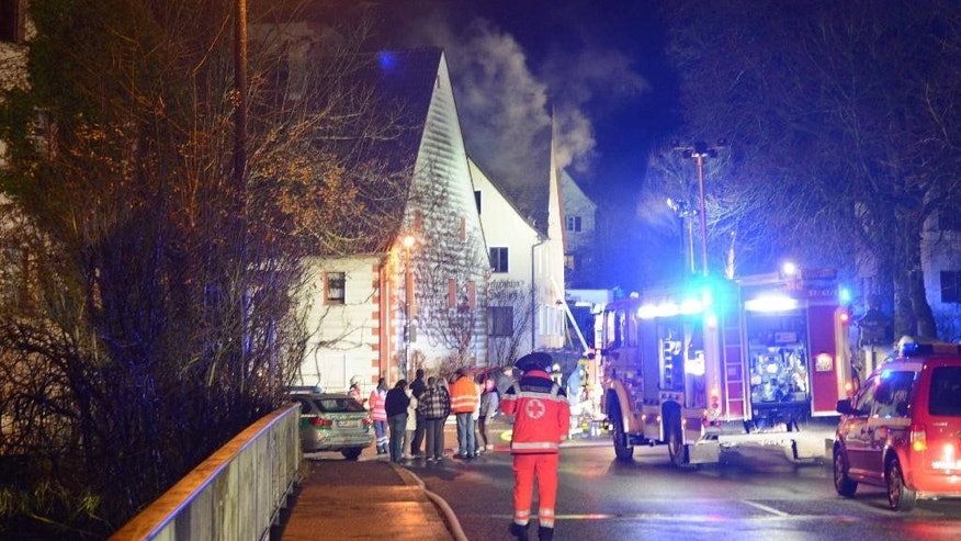 Firefighters stand near a building in Vorra, Germany, early  Friday Dec. 12, 2014.  Police say arsonists are suspected of setting fires at three empty buildings in Bavaria that had been earmarked to serve as accommodation for asylum seekers. The fires broke out late Thursday evening in Vorra, near Nuremberg. Police said Friday that anti-foreigner slogans and swastikas were found daubed at one site. There was no one in the buildings at the time. Police say the blazes were extinguished quickly but one firefighter was slightly injured.  (AP Photo/dpa, ToMa/dpa)