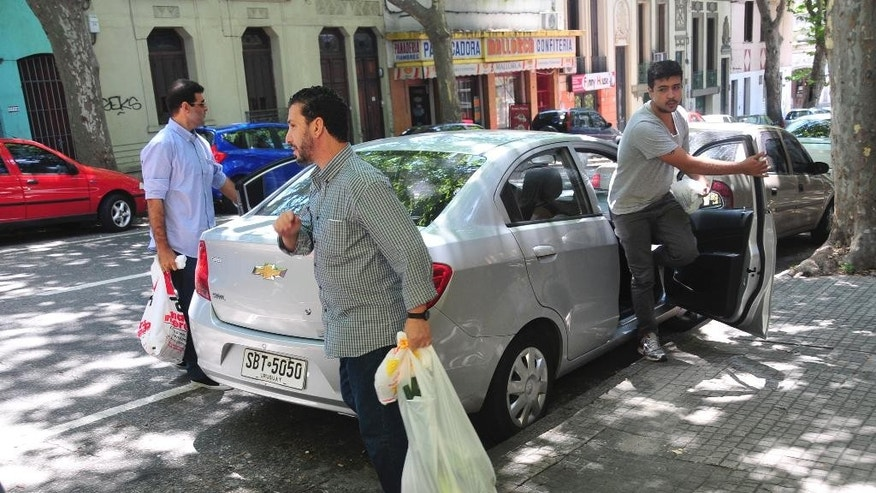 Adel bin Muhammad El Ouerghi from Tunisia, center, a former prisoner at Guantanamo Bay, exits a car carrying groceries accompanied by a member of PIT-CNT, one of Uruguay's workers unions, right, in a residential area of Montevideo, Uruguay, Thursday, Dec. 11, 2014. Six prisoners held for 12 years at Guantanamo Bay began their new lives in Uruguay after the United States flew them to the South American country as refugees amid a renewed push by President Barack Obama to close the prison. (AP Photo/Ines Guimaraens, Diario El Observador) URUGUAY OUT - NO USAR EN URUGUAY