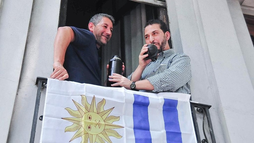 CORRECTS ID OF MAN AT LEFT.- A former prisoner at Guantanamo Bay, right,  stands drinking 'mate', a local herbal tea, on a balcony decorated with a flag of Uruguay in Montevideo, Uruguay, Thursday, Dec. 11, 2014.  The man is one of the six  prisoners held for 12 years at Guantanamo Bay who arrived last Sunday as refugees in Uruguay amid a renewed push by President Barack Obama to close the prison.  Among those transferred was Abu Wa'el Dhiab, a 43-year-old Syrian on a long-term hunger strike protesting his confinement who was at the center of a legal battle in U.S. courts over the military's use of force-feeding. The Pentagon identified the other Syrians sent to Uruguay on Saturday as Ali Husain Shaaban, 32; Ahmed Adnan Ajuri, 37; and Abdelahdi Faraj, 33. Also released were Palestinian prisoner Mohammed Abdullah Taha Mattan, 35, and 49-year-old Adel bin Muhammad El Ouerghi of Tunisia. The man at right is a member of PIT-CNT, one of Uruguay's workers union.(AP Photo/Ines Guimaraens/Diario El Observador) URUGUAY OUT - NOT FOR USE IN URUGUAY WEBSITES OR PUBLICATIONS