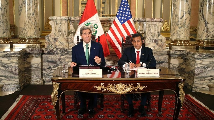 U.S. Secretary of State John Kerry, left, speaks to the press as he sits with Peru's President Ollanta Humala after a private meeting at the government palace in Lima, Peru, Thursday, Dec. 11, 2014. Kerry is in Lima, along with delegates from more than 190 countries, to work on drafts for a global climate deal that is supposed to be adopted next year in Paris. (AP Photo/Martin Mejia)
