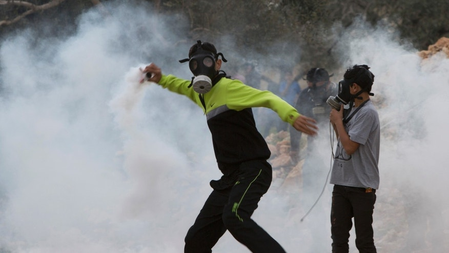 Dec. 12, 2014 - A Palestinian protester throws back a tear gas canister fired by Israeli soldiers during clashes following a protest against the nearby Jewish settlement of Kdumim, in the West Bank village of Kufr Qaddum.