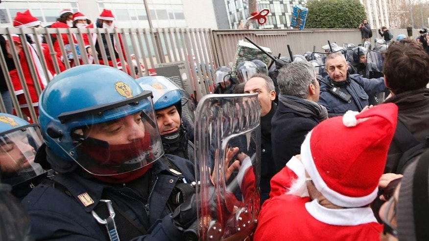 A student wearing a Santa's costumes is pushed away by a policemen during a protest in Milan, Italy, Friday, Dec. 12, 2014. Thousands of union workers and students staging a general strike marched Friday through more than 50 Italian cities to protest government reforms that they say erode workers' rights. The general strike, shutting down basic services across Italy, is the first ever by two of Italy's largest union confederations against a center-left government, which have traditionally cozied up to unions. Premier Matteo Renzi said the right to strike must be protected, but insisted his tougher line is necessary to return the economy to growth and create jobs. (AP Photo/Luca Bruno)