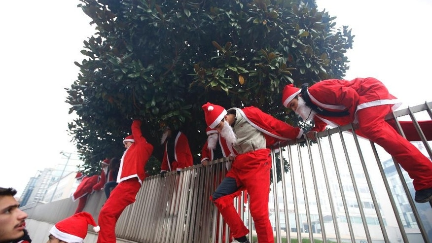 Students wearing Santa's costumes climb over the fence surrounding the Lombardy region building during a protest in Milan, Italy, Friday, Dec. 12, 2014. Thousands of union workers and students staging a general strike marched Friday through more than 50 Italian cities to protest government reforms that they say erode workers' rights. The general strike, shutting down basic services across Italy, is the first ever by two of Italy's largest union confederations against a center-left government, which have traditionally cozied up to unions. Premier Matteo Renzi said the right to strike must be protected, but insisted his tougher line is necessary to return the economy to growth and create jobs. (AP Photo/Luca Bruno)