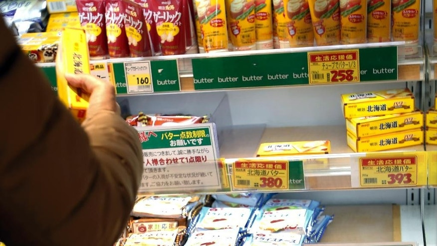 "In this Tuesday, Dec. 9, 2014 photo, a shopper picks up a packet of butter at a supermarket where a notice advises shoppers not to buy more than one in Tokyo. Worsening butter shortages are a symptom of deeply entrenched resistance to reforms Prime Minister Shinzo Abe will be struggling to deliver even if his party wins a stronger mandate for his ""Abenomics"" policies in an election Sunday, Dec. 14. (AP Photo/Shizuo Kambayashi)"