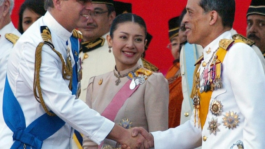 FILE - In this Aug. 31, 2007 file photo, Thailand's Crown Prince Maha Vajiralongkorn, right, accompanied by his royal consort Princess Srirasm, center, shakes hands with Britain's Prince Andrew during a parade at the Merdeka Square in Kuala Lumpur, marking Malaysia's 50 years of independence from Britain. The woman who was in line to become Thailand's next queen has relinquished her royal title following revelations last month that several members of her family were detained in a high-profile corruption scandal. A brief statement from the palace's Royal Gazette that was made public late Friday, Dec. 12, 2014 said Srirasm had asked permission to give up her royal status. (AP Photo/Lai Seng Sin, File)