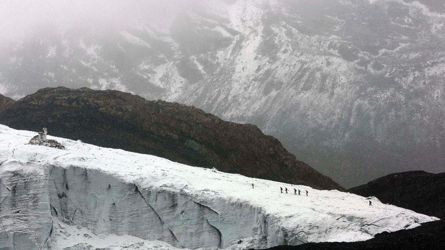 AP10ThingsToSee - Members of the glaciology unit of Peru's national water authority walk on the Pastoruri glacier in Huaraz, Peru, Thursday, Dec. 4, 2014. The glaciology unit is studying the measurement of ice thickness. (AP Photo/Rodrigo Abd)