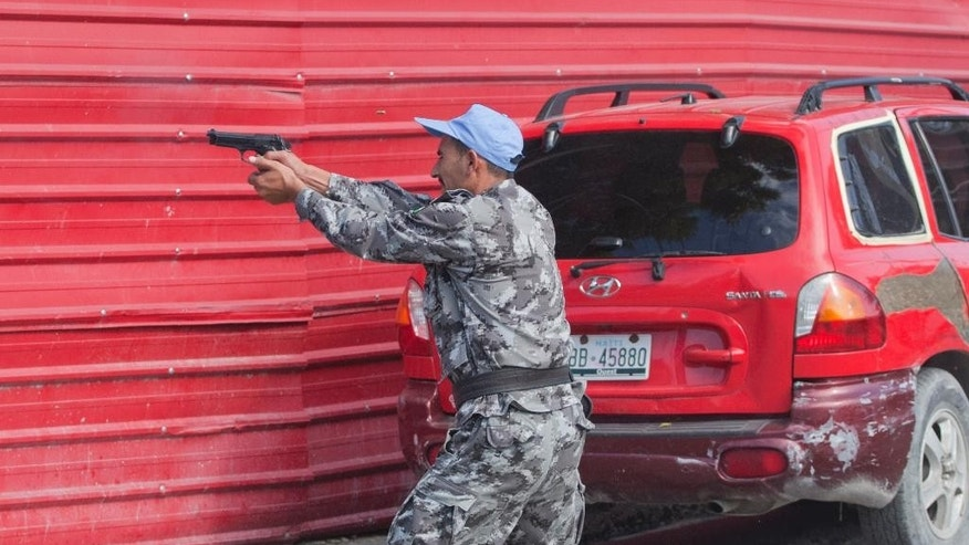 A Jordanian soldier from the U.N. peacekeeping force fires a gun at protesters demanding the resignation of Haiti's President Michel Martelly and Prime Minister Laurent Lamothe in Port-au-Prince, Haiti, Friday, Dec. 12, 2014. The protest occurred hours before President Michel Martelly was scheduled to talk about a commission report that calls for a new consensus government. (AP Photo/Dieu Nalio Chery)