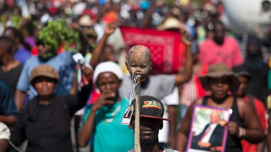 A protester carries a doll's head with a marijuana cigar in its mouth and an image of Haiti's former president Jean Bertrand Aristide hanging from a string during an anti-government protest demanding the resignation of Haiti's President Michel Martelly and Prime Minister Laurent Lamothe in Port-au-Prince, Haiti, Friday, Dec. 12, 2014. ( AP Photo/Dieu Nalio Chery)