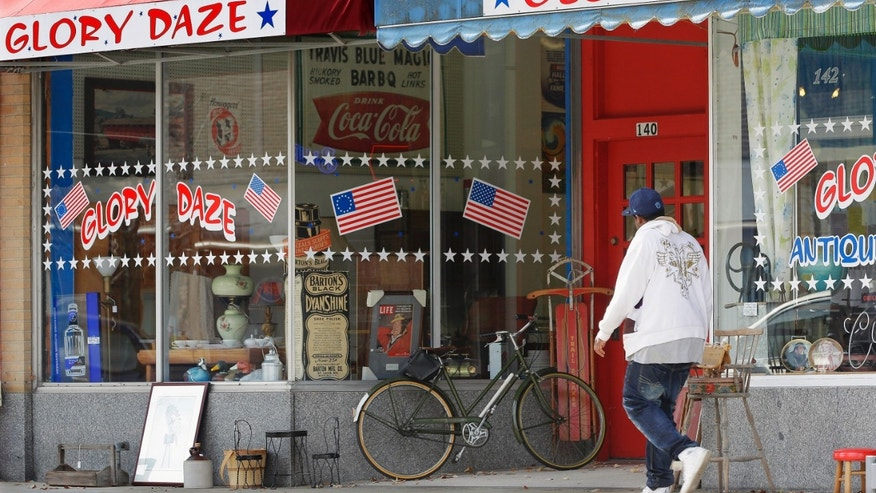 In this Oct. 23, 2014 photo, people walk past one of the popular businesses in downtown in Danville, Ill., where there still are many vacant buildings. Many young people have moved away as manufacturers that provided thousands of well-paying, middle class jobs have closed, but the city is working to attract new businesses and give residents a reason to stay. (AP Photo/Seth Perlman)
