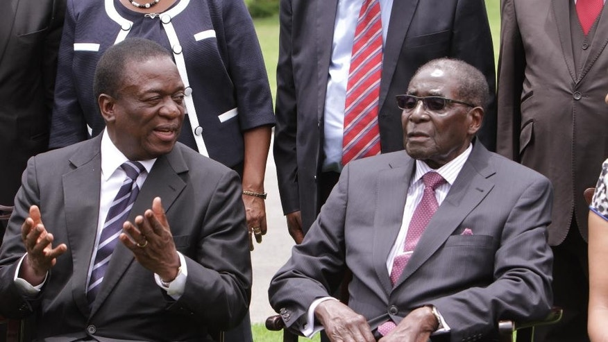 Emmerson Mnangagwa, left, Vice President of Zimbabwe chats with Zimbabwean President Robert Mugabe after the swearing in ceremony at State House in Harare, Friday, Dec, 12, 2014. Mnangagwa was sworn  in following a cabinet reshuffle that saw former deputy President Joice Mujuru dismissed from her post, over allegations that she plotted to remove the Zimbabwean President from power. (AP Photo/Tsvangirayi Mukwazhi)