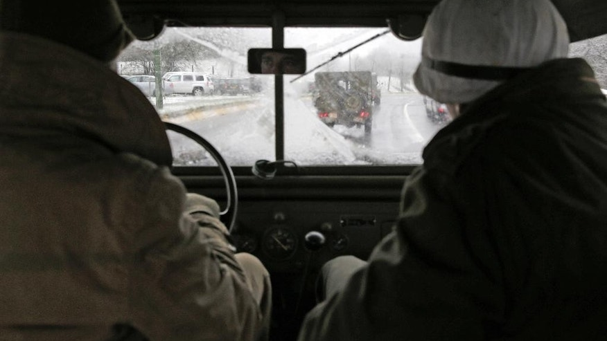 Re-enactors dressed as U.S. WWII soldiers drive in snowy weather conditions, during the 70th anniversary of the Battle of the Bulge or the Ardennes Offensive, in Bastogne, Southeastern Belgium, Saturday, Dec. 13, 2014. The Battle of the Bulge was fought in dense forests and narrow valleys of the Belgian and Luxembourg Ardennes and was one of the bloodiest battles of World War II. (AP Photo/Yves Logghe)