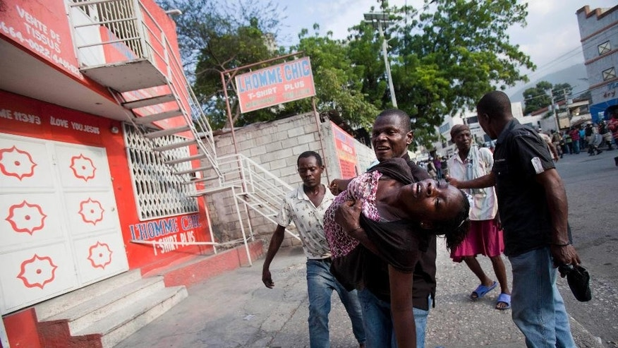 A woman who passed out from tear gas is carried away after tear gas was fired near her home during clashes between anti-government protesters and he National Police in Port-au-Prince, Haiti, Saturday, Dec. 13, 2014. Haiti's capital has endured a growing number of violent demonstrations in which protesters are demanding long-delayed elections and the resignations of Prime Minister Laurent Lamothe as well as President Michel Martelly. The protests also spread to other towns, including Gonaives and Cap-Haitien. (AP Photo/Dieu Nalio Chery)