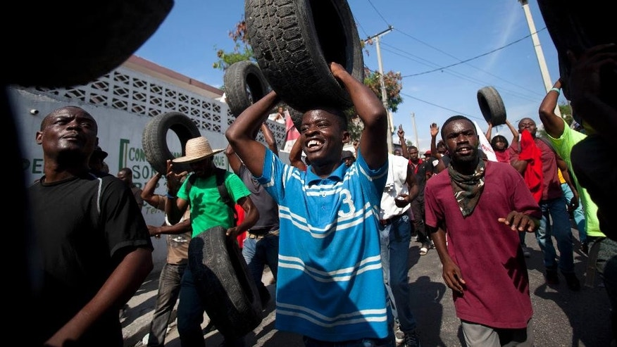 Anti-government protesters carry tires to use for burning road blocks in Port-au-Prince, Haiti, Saturday, Dec. 13, 2014. Haiti's capital has endured a growing number of demonstrations in which protesters are demanding long-delayed elections and the resignations of Prime Minister Laurent Lamothe as well as President Michel Martelly. (AP Photo/Dieu Nalio Chery)