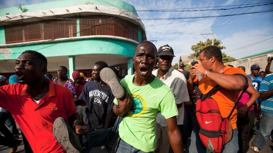 Anti-government protesters carry the body of a demonstrator who was shot to death during clashes with the National Police in Port-au-Prince, Haiti, Saturday, Dec. 13, 2014. Haiti's capital has endured a growing number of violent demonstrations in which protesters are demanding long-delayed elections and the resignations of Prime Minister Laurent Lamothe as well as President Michel Martelly. (AP Photo/Dieu Nalio Chery)