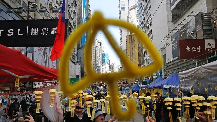 Yellow umbrella decorations are hanged by protesters in the Causeway Bay shopping district, one of the occupied areas by pro-democracy protesters in Hong Kong Saturday, Dec. 13, 2014. Traffic was back to normal Friday in Hong Kong's financial district after authorities demolished a protest camp at the heart of the city's 2 and a half month pro-democracy movement. (AP Photo/Kin Cheung)
