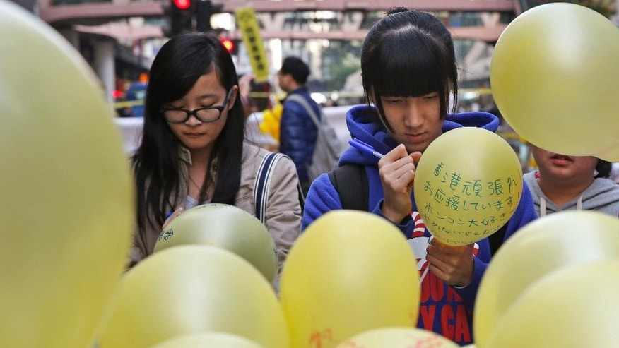 People write their support messages on the balloon in the Causeway Bay shopping district, one of the occupied areas in Hong Kong Saturday, Dec. 13, 2014. Traffic was back to normal Friday in Hong Kong's financial district after authorities demolished a protest camp at the heart of the city's 2 and a half month pro-democracy movement. (AP Photo/Kin Cheung)