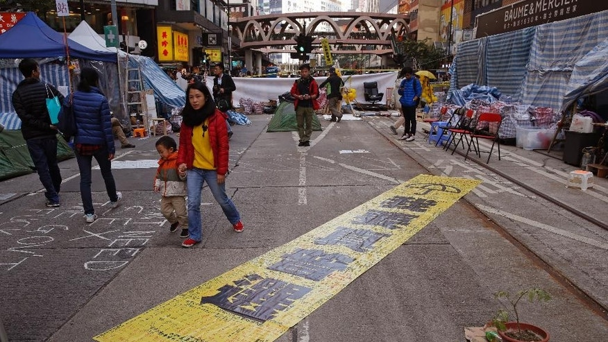 "The yellow banner reads "" I want genuine universal suffrage."" is displayed by protesters in the Causeway Bay shopping district, one of the occupied areas in Hong Kong Saturday, Dec.13, 2014. Traffic was back to normal Friday in Hong Kong's financial district after authorities demolished a protest camp at the heart of the city's 2 and a half month pro-democracy movement. (AP Photo/Kin Cheung)"