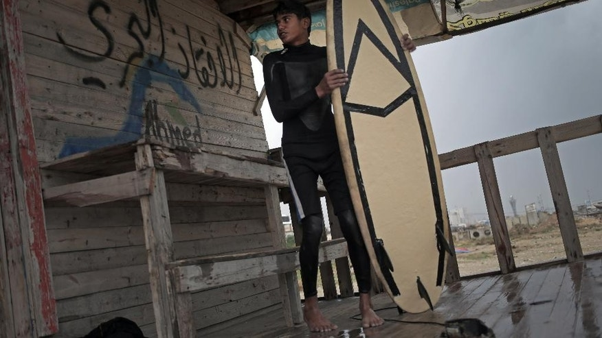"In this Sunday, Nov. 23, 2014 photo, Palestinian Ahmed Abu Ghanim, 16, holds his surf board while standing next to Arabic writing that reads ""lifeguard,"" after surfing at the beach of Gaza City. Despite a long Mediterranean coastline, Gaza only has about two dozen surfers who, according to the Facebook page of the Gaza Surf Club, pursue the sport to ""forget about the hardships of living in Gaza.'' (AP Photo/Khalil Hamra)"