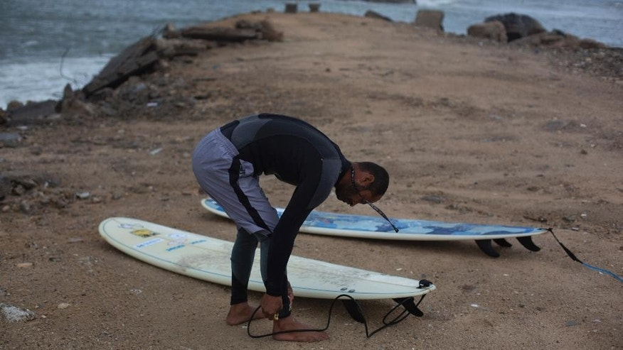 "In this Thursday Nov. 27, 2014 photo, Palestinian Mohammed Abu Jayyab, 41, prepares to surf at the beach in Gaza City. Despite a long Mediterranean coastline, Gaza only has about two dozen surfers who, according to the Facebook page of the Gaza Surf Club, pursue the sport to ""forget about the hardships of living in Gaza.'' (AP Photo/Khalil Hamra)"