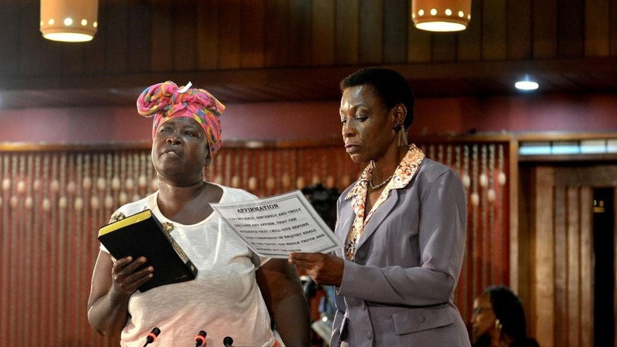 "In this Dec. 8, 2014 photo, market vendor Adina Derby takes an oath before testifying to a truth commission about the 2010 state of emergency when security forces conducted a raid to capture a gang kingpin that killed at least 76 civilians and one soldier, at a conference center in Kingston, Jamaica. ""They come with blood in their eyes to kill off everybody!"" Derby exclaimed, describing how she was shot in the back while trying vainly to save her wounded 20-year-old son by pushing him on a handcart to a nearby hospital. (AP Photo/David McFadden)"