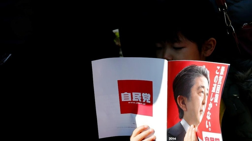 "FILE - In this Sunday, Dec. 7, 2014 file photo, a girl reads a brochure of the Liberal Democratic Party manifesto featuring a portrait of the party leader and Prime Minister Shinzo Abe and the party slogan ""Economic recovery, this is the only way"" during a campaign rally for the lower house election in Tokyo. Abe is counting on a landslide victory in a snap election Sunday, Dec. 14 that will likely return his ruling coalition to power with an even bigger majority, empowering him to pursue an ambitious agenda of political and economic reforms. ""This is the only way"" is the slogan Abe is driving home in his campaign speeches. For Japanese voters, that is probably the case. (AP Photo/Shizuo Kambayashi, File)"