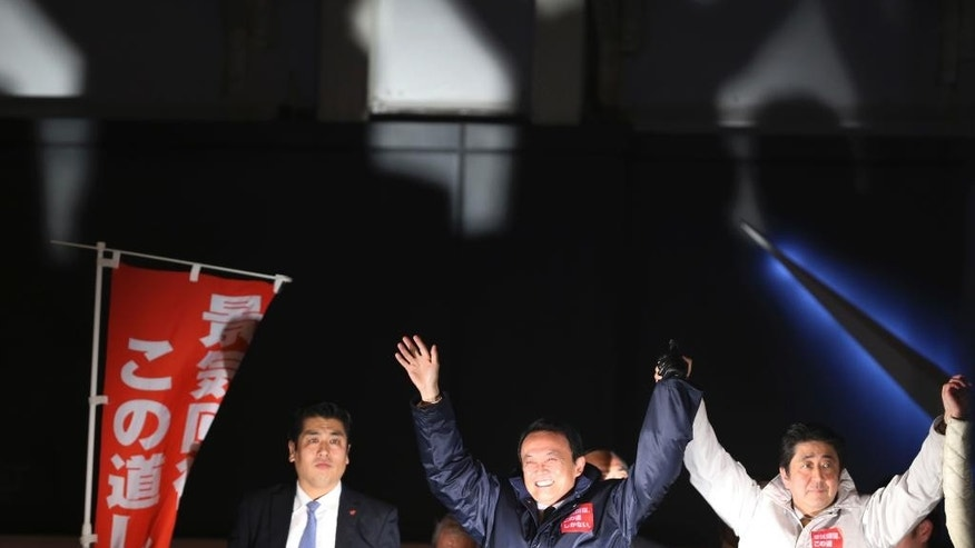 Japan's Prime Minister Shinzo Abe, right, and Finance Minister Taro Aso,  center, wave to the crowd, during their election campaign of the ruling Liberal Democratic Party in Tokyo,  a day before Parliament's lower house election Saturday, Dec. 13. 2014.  Prime Minister Abe is counting on a landslide victory in parliamentary elections Sunday that will likely return his ruling coalition to power with an even bigger majority, empowering him to pursue an ambitious agenda of political and economic reforms.(AP Photo/Koji Sasahara)