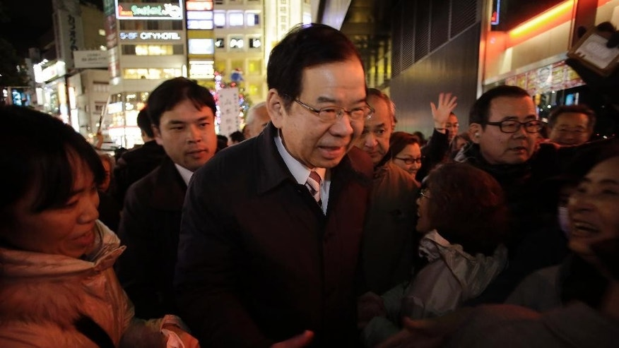 Kazuo Shii, head of the opposition Japanese Communist Party, shakes hands with supporters during the last day campaign for Sunday's parliamentary elections in Tokyo, Saturday, Dec. 13, 2014. (AP Photo/Eugene Hoshiko)