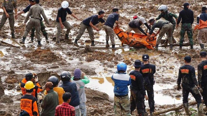 Rescuers remove the body of a victim of landslides that swept away houses in Jemblung village, Central Java, Indonesia, Saturday, Dec. 13, 2014. Scores of people died and more than 100 are missing following landslides caused by heavy rain in central Indonesia on Friday, local government officials said Saturday. (AP Photo/Bayu Nur)