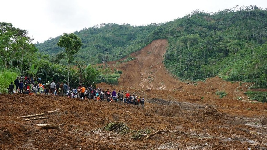 Villagers and rescuers examine the site where a landslide swept away houses in Jemblung village, Central Java, Indonesia, Saturday, Dec. 13, 2014. Torrential rains set off the mudslide down the hills into the village in central Indonesia, killing scores of people with more than 100 missing. (AP Photo/Bayu Nur)