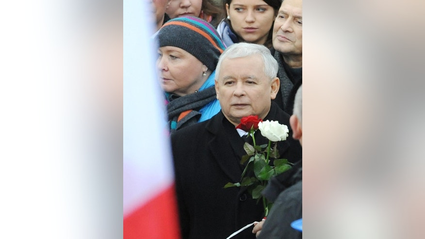 Leader of the main opposition party, the conservative Law and Justice Party, Jaroslaw Kaczynski holds red and white roses, in Poland's national colors,  as thousands of his supporters gather at the Three Crosses square in Warsaw, Poland, Saturday, Dec. 13, 2014, to protest the results of recent local elections, which Kaczynski says were falsified.  (AP Photo/Alik Keplicz)