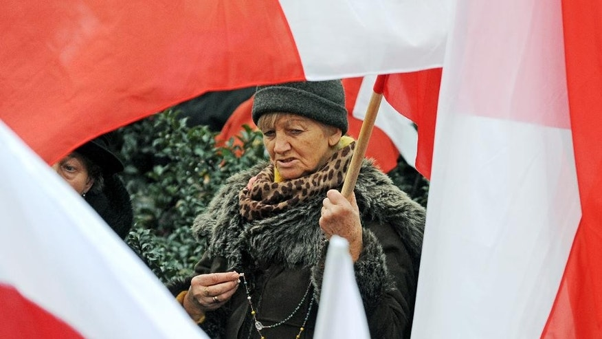 A woman seen between Polish national flags prays holding a rosary during  a prayer   prior to  a demonstration  in Warsaw, Poland, Saturday, Dec. 13, 2014,  Thousands of supporters of a conservative opposition party in Poland are protesting the results of recent local elections, which party leader Jaroslaw Kaczynski says were falsified.  (AP Photo/Alik Keplicz)