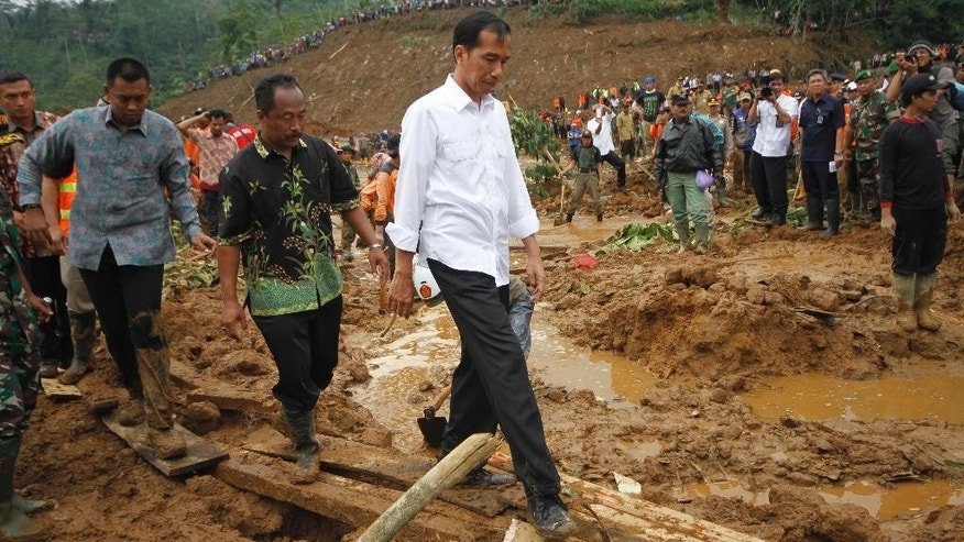 Indonesian President Joko Widodo inspects the site of a  landslide that swept away a village in Jemblung, Central Java, Indonesia, Sunday, Dec. 14, 2014. Rescuers pulled more bodies from the debris Sunday after heavy rain in central Indonesia loosened soil and collapsed a hill, setting off the landslide that left dozens of people dead or missing. Widodo arrived at the scene Sunday. He pledged to relocate the hundreds of people left homeless by the disaster, and assured that the government would help provide aid for those who were injured. (AP Photo/A.K. Hendratmo)