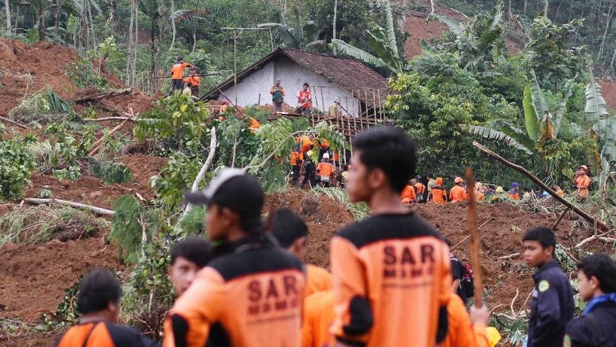 Rescuers search for the victims of a landslide that swept away a village in Jemblung, Central Java, Indonesia, Sunday, Dec. 14, 2014. Rescuers pulled more bodies from the debris Sunday after heavy rain in central Indonesia loosened soil and collapsed a hill, setting off the landslide that left dozens of people dead or missing. (AP Photo/N. Agung Nugroho)