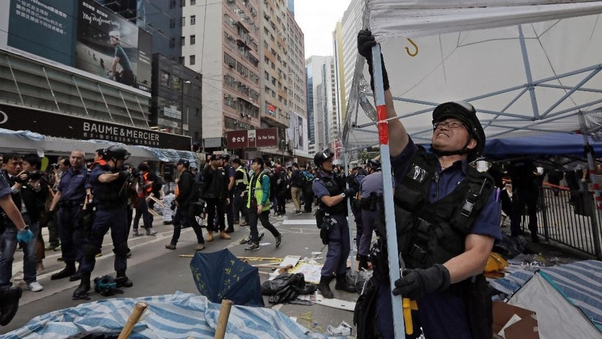 Police officers take down a tent on a main road in the occupied areas at Causeway Bay district in Hong Kong Monday, Dec 15, 2014. Hong Kong police pulled down barricades Monday and folded up tents at the third and final pro-democracy protest camp, putting an end to demonstrations that have blocked traffic in the southern Chinese city's streets for 2 and a half months. (AP Photo/Vincent Yu)