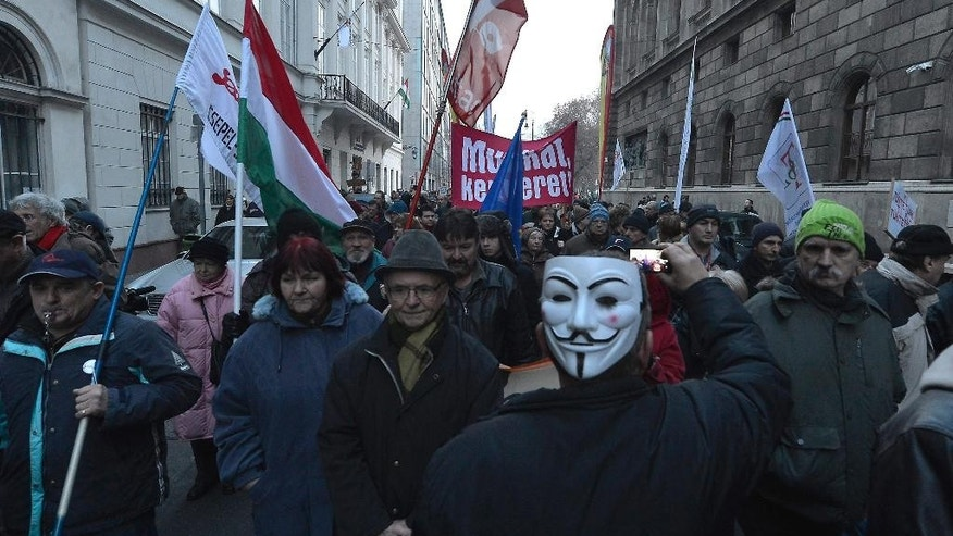 Protestors march towards the Parliament building to protest against the planned budget of the year 2015 in Budapest, Hungary, Sunday, Dec. 14, 2014. Around 2,500 Hungarians protest outside Parliament Sunday against alleged government corruption, austerity measures and deteriorating social welfare programs, according to protest organizer Zoltan Vajda, saying the 2015 state budget to be approved by lawmakers Monday was unworthy of Hungary. (AP Photo/MTI, Tibor Illyes)